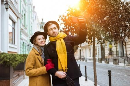 beautiful young couple taking selfie in autumn outfit