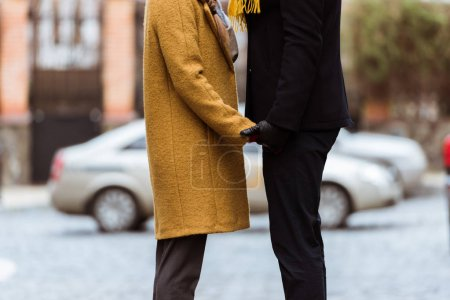 cropped image of holding hands couple in autumn outfit