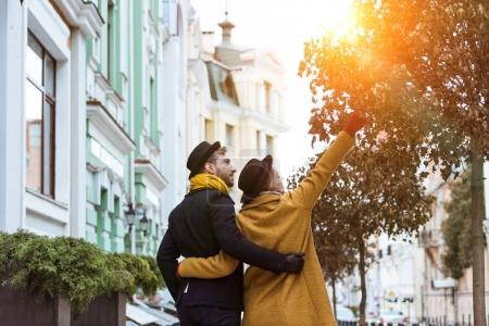 back view of young couple hugging and walking at street