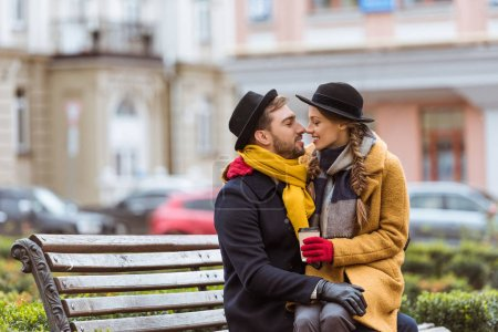 beautiful couple sitting on bench with coffee cup