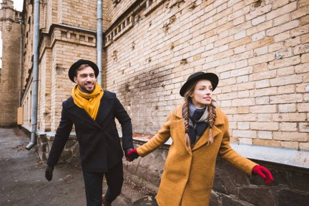 cute young couple holding hands and running beside old building