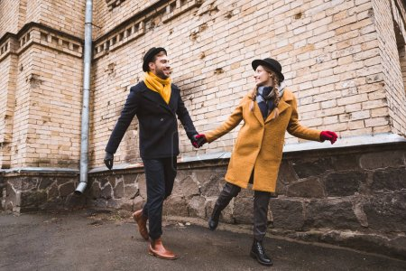 Photo for Cute young couple holding hands and running beside old building - Royalty Free Image