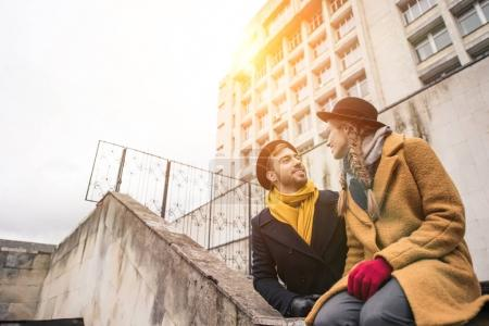 attractive young couple in autumn outfit looking at each other