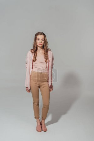 full length view of beautiful young woman in looking at camera isolated on grey