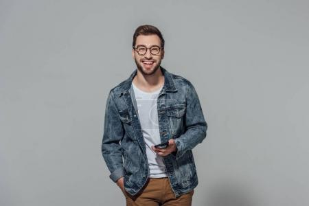 Photo for Cheerful young man holding smartphone and smiling at camera isolated on grey - Royalty Free Image