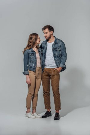 full length view of smiling young couple in denim jackets looking at each other isolated on grey