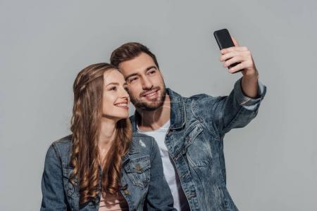 Photo for Happy young couple in denim jackets taking selfie with smartphone isolated on grey - Royalty Free Image