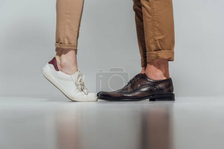 partial view of male and female legs in footwear with reflection on grey