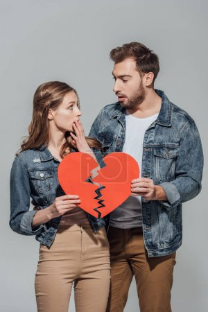 Photo for Upset couple holding pieces of broken heart symbol and looking at each other isolated on grey - Royalty Free Image