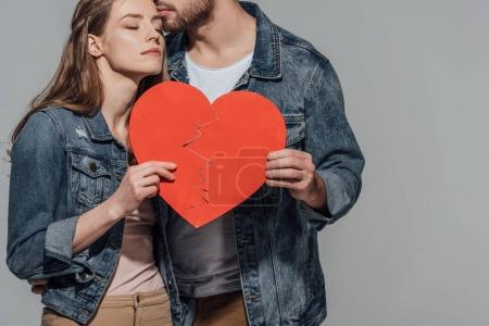 Photo for Cropped shot of young couple holding parts of broken heart symbol together and kissing isolated on grey - Royalty Free Image