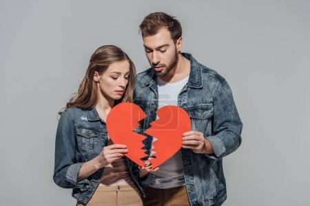 Photo for Upset young couple holding parts of broken heart symbol isolated on grey - Royalty Free Image