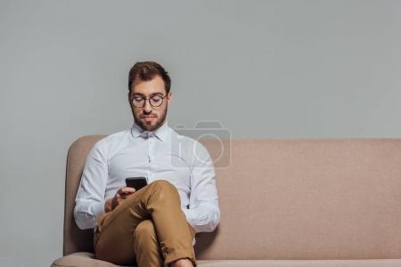 Photo pour Hansome jeune homme à lunettes à l'aide de smartphone tout en étant assis sur le canapé isolé sur fond gris - image libre de droit
