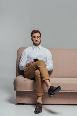 young man in eyeglasses holding smartphone and looking at camera while sitting on sofa isolated on grey
