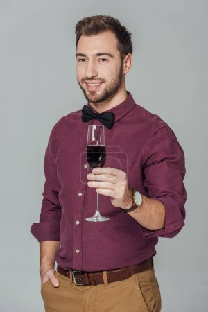 Photo for Handsome stylish young man holding glass of red wine and smiling at camera isolated on grey - Royalty Free Image