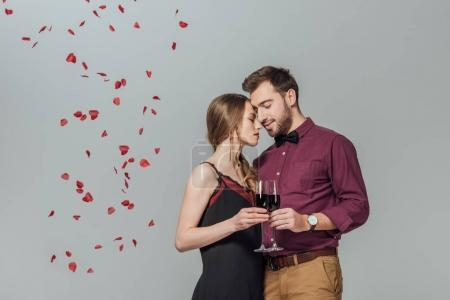 beautiful young couple holding glasses of red wine and rose petals falling isolated on grey