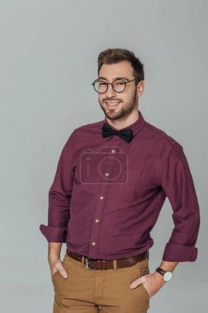 stylish young man in eyeglasses standing with hands in pockets and smiling at camera isolated on grey