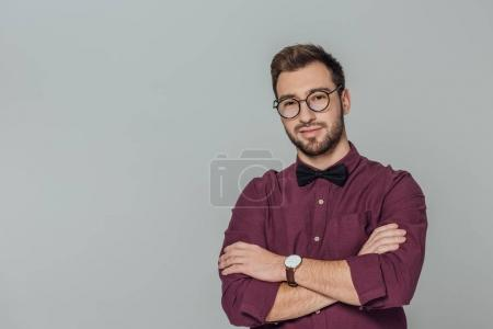 Photo for Stylish young man in eyeglasses standing with crossed arms and smiling at camera isolated on grey - Royalty Free Image