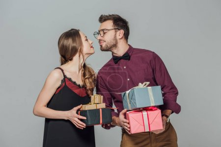 fashionable happy young couple holding gift boxes and able to kiss isolated on grey