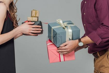 cropped shot of young couple holding gift boxes isolated on grey