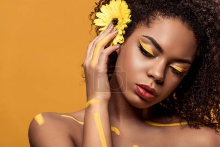 Beautiful african american woman with artistic make-up and gerbera in hair dreaming isolated on orange background