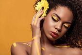 """Постер, картина, фотообои """"Красивая афро-американских женщина с художественным макияжа и герберы в волосы мечтает, изолированные на оранжевом фоне"""""""