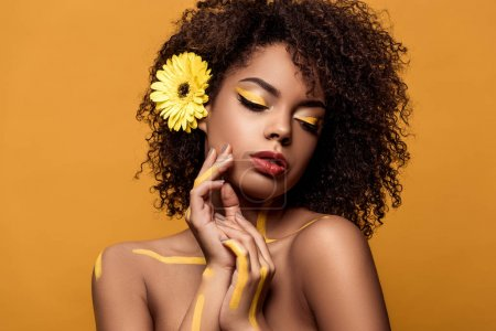 Stylish african american woman with artistic make-up and gerbera in hair holds hands near face isolated on orange background