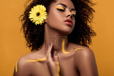 Stylish african american woman with artistic make-up and gerbera in hair tenderly touches her skin isolated on orange background