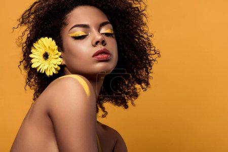Photo pour Jeune femme afro-américaine tendre avec maquillage artistique et gerbera dans les cheveux isolés sur fond orange - image libre de droit