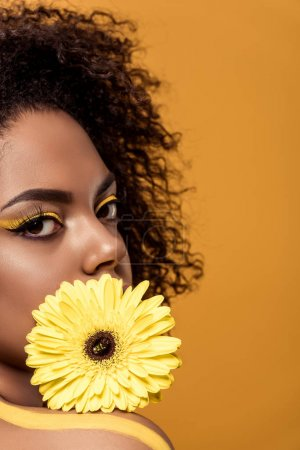 Attractive young african american woman with artistic make-up holds yellow gerbera flower isolated on orange background