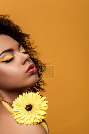 Young bright african american woman with artistic make-up holds yellow gerbera flower isolated on orange background