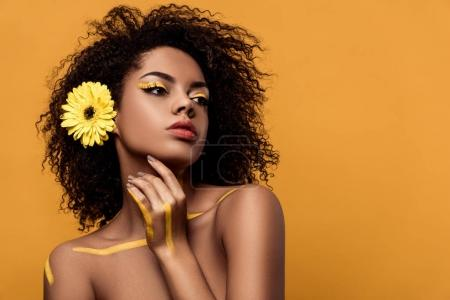 Young sensual african american woman with artistic make-up and gerbera in hair holds hand by her face isolated on orange background