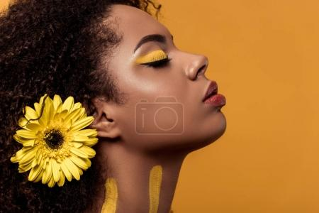 Stylish african american woman with artistic make-up and gerbera in hair dreaming isolated on orange background