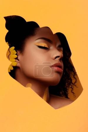 Stylish african american woman with artistic make-up and gerbera in hair in cupcake frame