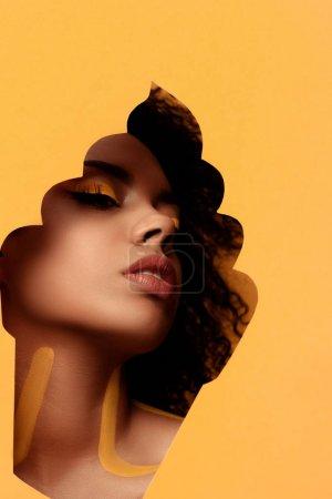 Joven mujer afroamericana sensual con maquillaje artístico y gerbera en cabello en marco de magdalena