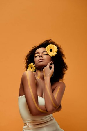 Photo for Young tender african american woman with artistic make-up and gerbera in hair isolated on orange background - Royalty Free Image