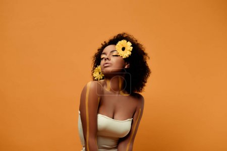 Photo for Young sensual african american woman with artistic make-up and gerbera in hair isolated on orange background - Royalty Free Image