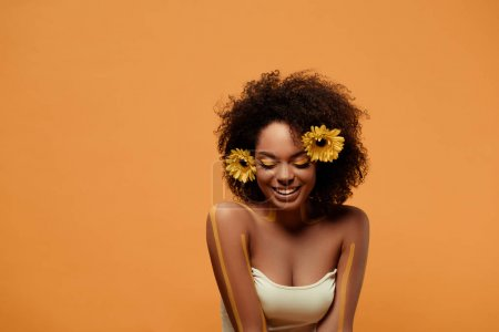 Young laughing african american woman with artistic make-up and gerbera in hair isolated on orange background