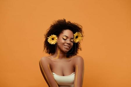 Photo for Young smiling african american woman with artistic make-up and gerbera in hair isolated on orange background - Royalty Free Image