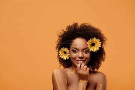 Foto de Joven sonriente mujer afroamericana con maquillaje artístico y gerbera en pelo aislado sobre fondo naranja - Imagen libre de derechos