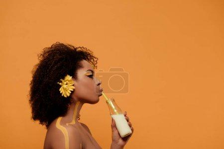 Joven mujer afroamericana sensual con maquillaje artístico y gerbera en el cabello bebiendo leche de botella aislada sobre fondo naranja
