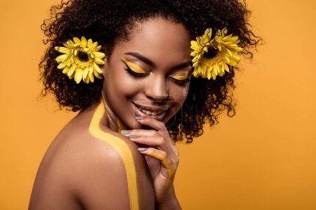 Photo for Young sensual african american woman with artistic make-up and gerberas in hair isolated on orange background - Royalty Free Image