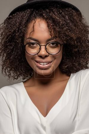 Young smiling african american woman in white shirt wearing glasses and hat isolated on grey background