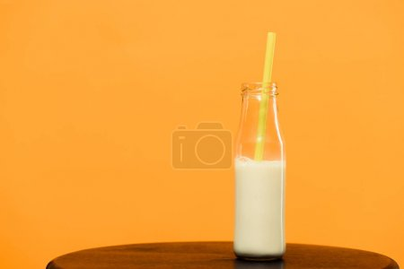 Milk drink in bottle with straw isolated on orange background