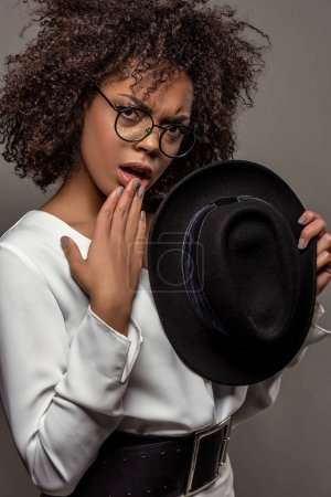 Young perplexed african american woman in white shirt wearing glasses and holding hat isolated on grey background