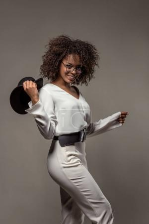 Stylish african american woman in white clothes smiling and waving black hat isolated on grey background