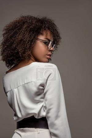 Elegante mujer afroamericana en camisa blanca con gafas aisladas sobre fondo gris