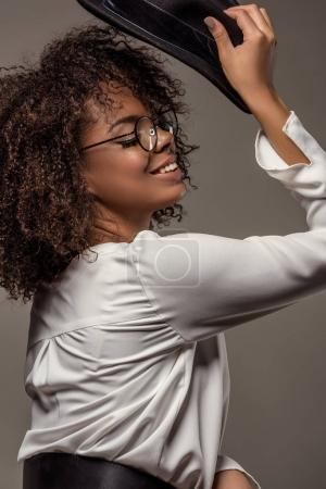 Attractive young american woman in white shirt wearing glasses pits black hat on isolated on grey background