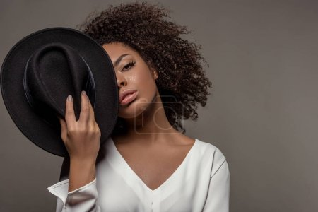 Attractive young african american woman in white shirt holding black hat over half of her face isolated on grey background
