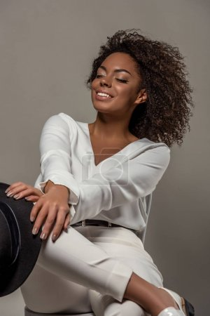 Young sensual african american woman in white clothes smiling and holding black hat isolated on grey background