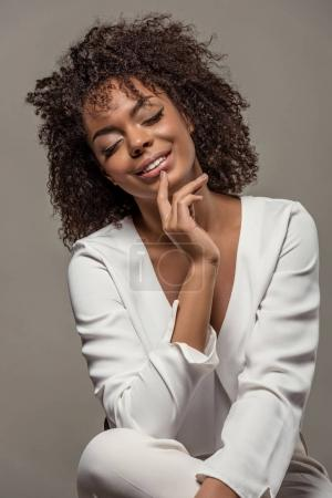 Young sensual african american woman in white shirt with finger on lips isolated on grey background